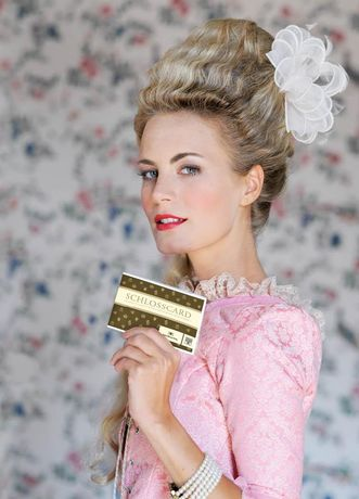 Eine kostümierte Dame präsentiert die Schlosscard