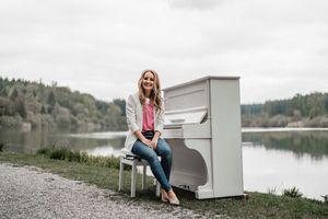 Judith Mutschler am weißen Klavier - vor einem See fotografiert
