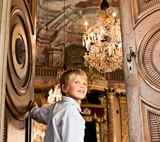 Image: A young boy opens a door at Ludwigsburg Residential Palace