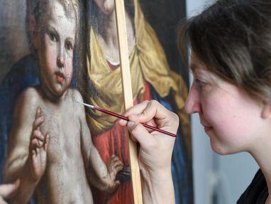Eine Frau malt auf einem alten Bild